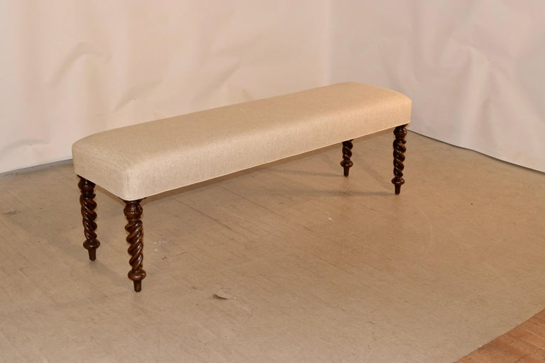 19th century upholstered bench from England with newly upholstered seat in linen finished with single welt decoration, supported upon mahogany hand-turned flame twist feet.