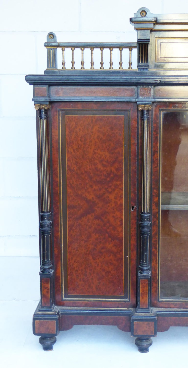 For sale is a good quality Victorian Aesthetic Movement amboyna and ebonised sideboard by Gillow, with a shelved gallery back above a pair of glazed doors enclosing velvet lined shelves flanked by two paneled doors projecting Corinthian fluted