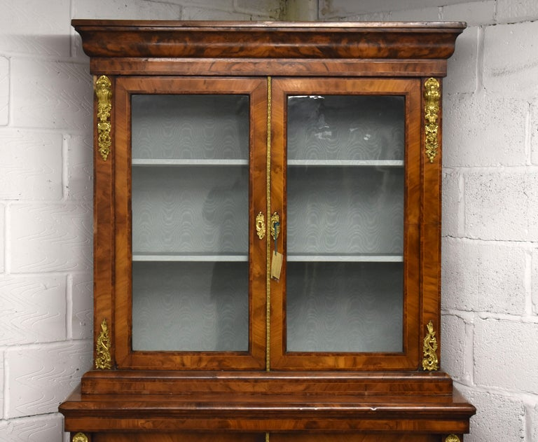 Selling is a superb quality Victorian burr walnut bookcase. The bookcase is banded in various woods. The top of the bookcase has ormolu mounts on each corner and glazed doors and sides and encloses two shelves, and has ormolu beading to the edge of