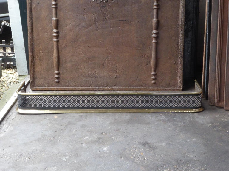 19th century English Victorian fireplace fender. The fender is made of polished brass and iron. The fender is in a good condition and is fully functional.