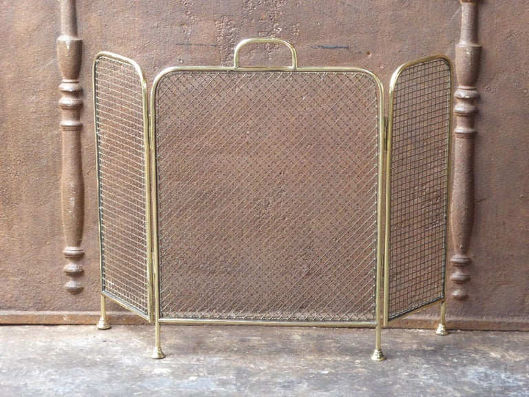 19th century English Victorian fireplace screen made of polished brass and iron mesh.