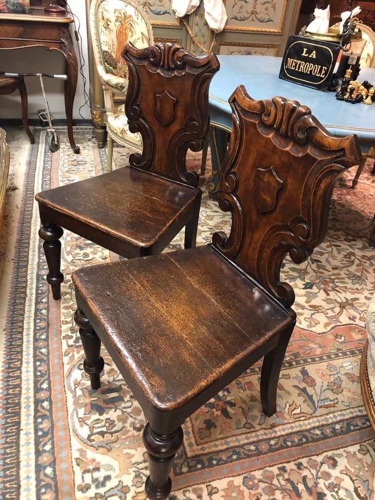 A pair of Victorian oak hall chairs, each with a scroll carved back, centred with a vacant shield, on turned front legs. England, circa 1860 From the private collection of Sir J. Lever.