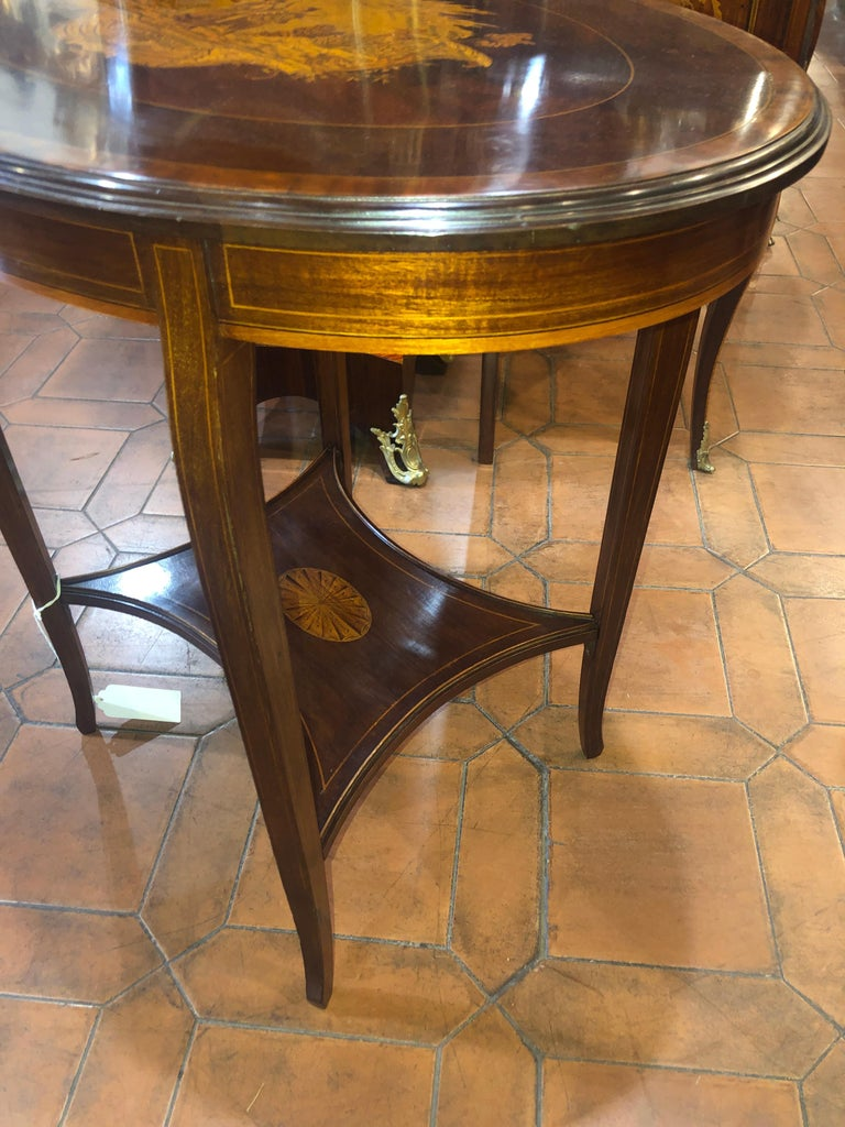 English oval table, finely inlaid with characters, of excellent workmanship. End of the Victorian period, circa 1890. In mahogany wood and inlays in fruitwood, details finished in ink.
