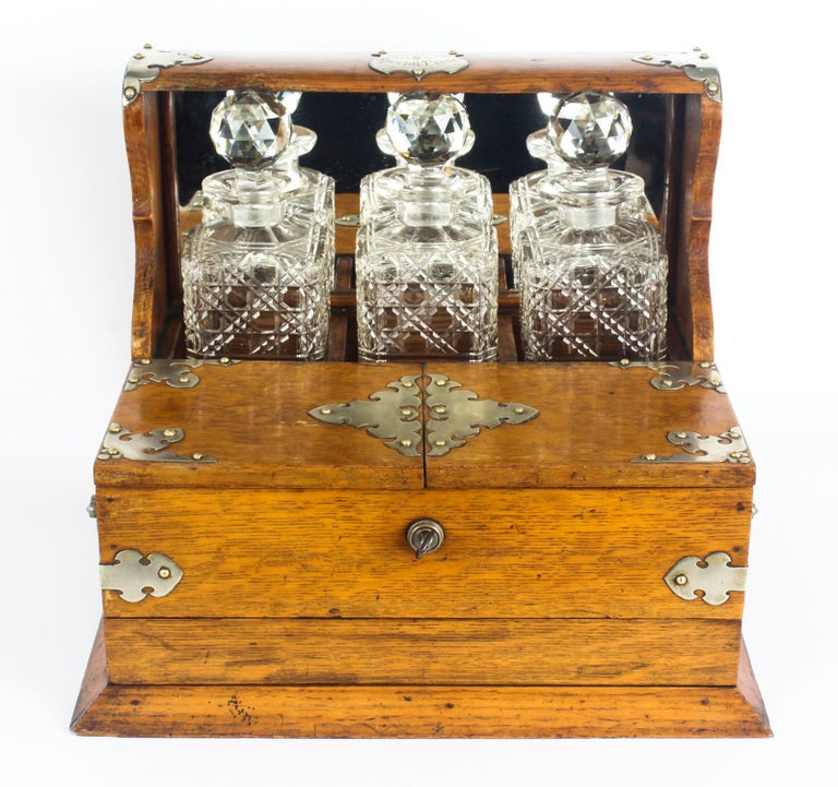 This is a superb antique Victorian oak cased three decanter tantalus with decorative silver plated cut brass mounts, shield marked