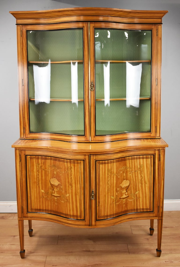 For sale is a fine 19th century satinwood serpentine display cabinet, inlaid with ebony stringing and edged with ebonized moulding, the upper section has a moulded cornice above to glazed doors opening to shelves. The base section, with well swept