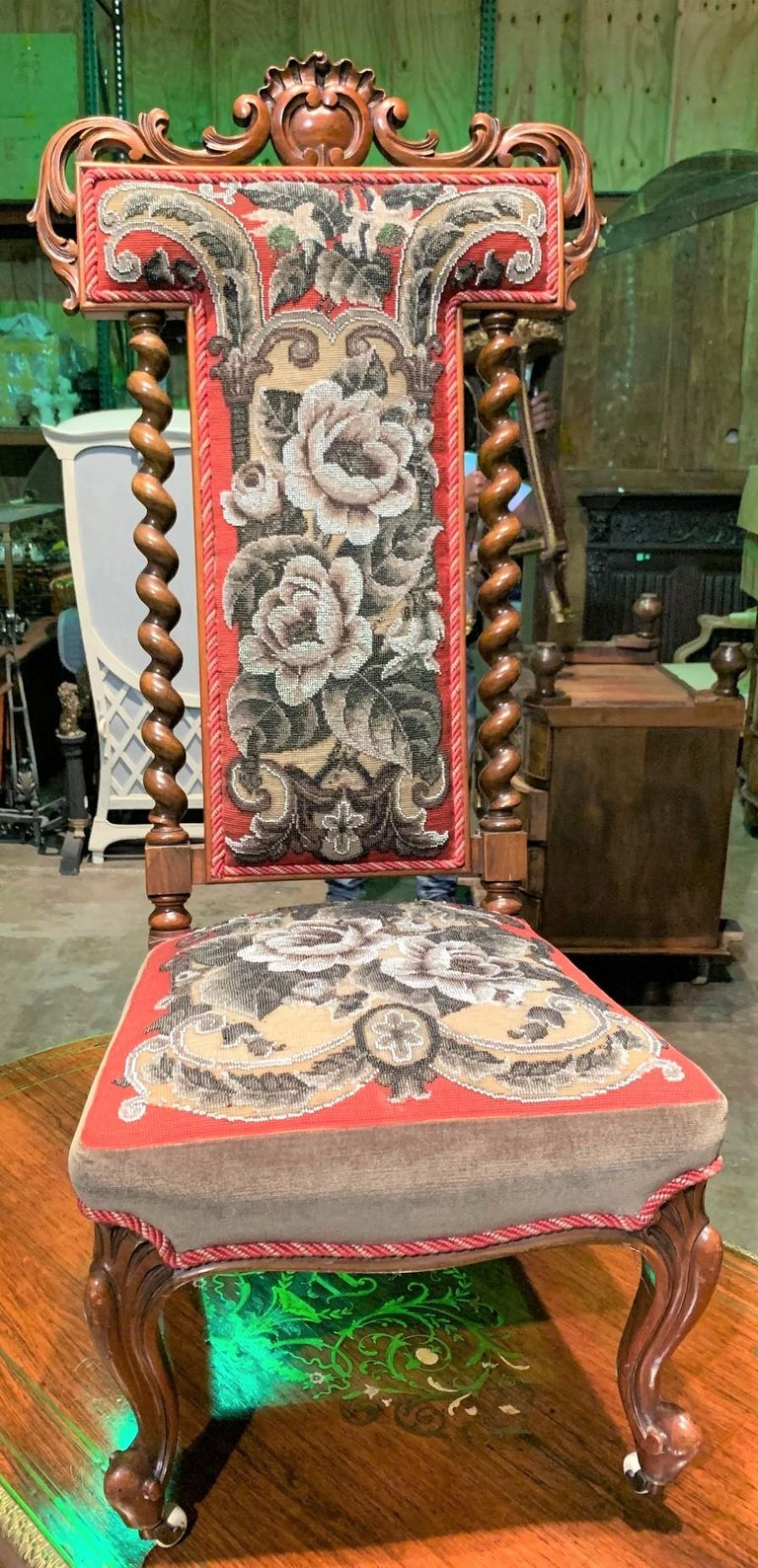 Excellent quality and scarce 19th century English Victorian mahogany ladies slipper chair upholstered in a fine needlepoint fabric. The crested back superbly carved in a foliate motif and flanked by barley twist columns. Having splayed back legs and