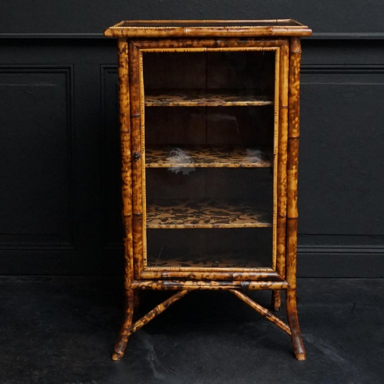 Nice little antique Victorian tiger-bamboo cabinet with lacquered top and original gilt relief wallpaper on all three interior shelves, the bottom and the sides.