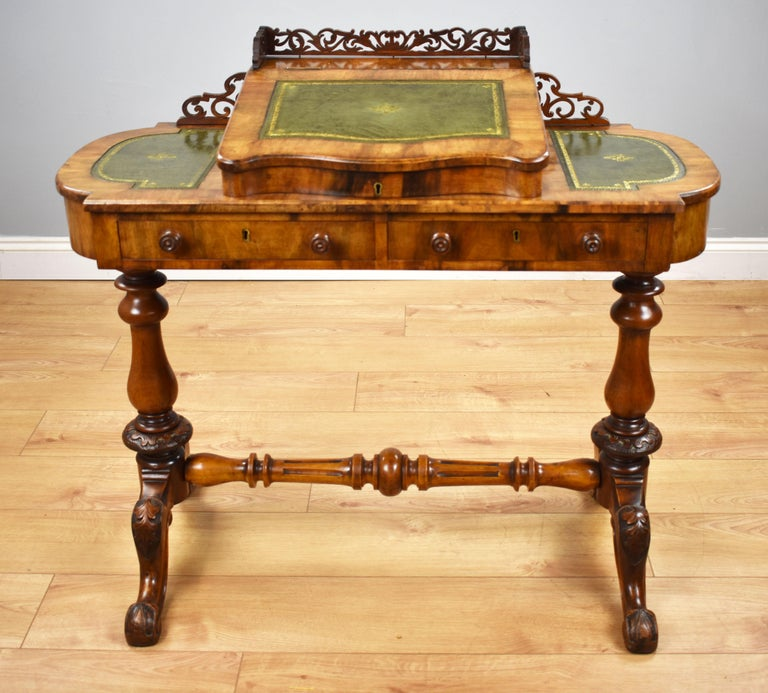 For sale is a Victorian walnut writing table, with an ornate fretwork gallery, above a sloped and rising writing surface inset with a green leather skiver, rising to reveal storage space. This is flanked by two more leather inserts, all with