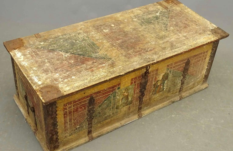 19th C. paint decorated blanket box or coffer. The front panel has a later added decoupage which has since been partially lost. This antique trunk, with its rectangular-shaped body, features original hand painted decorations about the top front