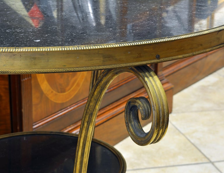 This French Empire gueridon table of the period features a black marble top beautifully edged by an ornate bronze gallery resting on three elegantly curved legs ending in paw feet with casters and united first by a second tier bronze edged marble