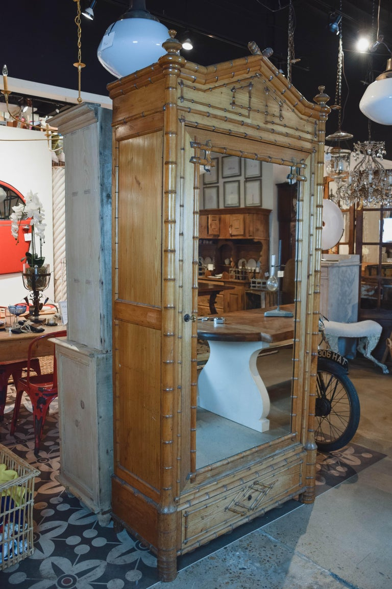 Found in England, this 19th century faux bamboo wardrobe/armoire is constructed in pine simulating bamboo. The cabinet has a large mirrored door with key that when open reveals four shelves for storage along with a drawer at the bottom. This piece
