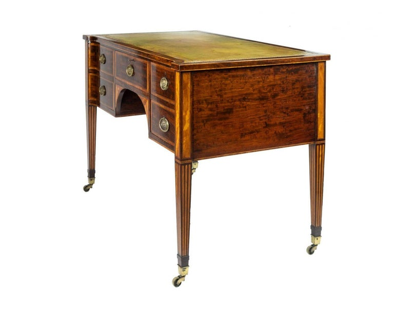 19th century figured mahogany writing desk with tooled leather inset top, the central frieze drawer flanked by a pair of cupboards, on square tapering legs inlaid with satinwood, stamped 'Wright & Mansfield, 104 Bond Street. Wright & Mansfield, the