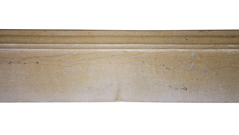 A fine European antique fireplace mantelpiece in a plain waxed limestone. A smooth ancient surface. It was built in the 19th century in the French the Burgundy region. Elegant, classy and not expensive for a timeless chique word interior design