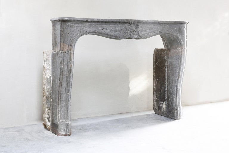 Beautiful antique fireplace from gray marble stone of the 19th century. This fireplace is in the style of Louis XV and has a shell in the middle. A beautiful decorative fireplace with beautiful lines. A fireplace that fits in many interiors in terms