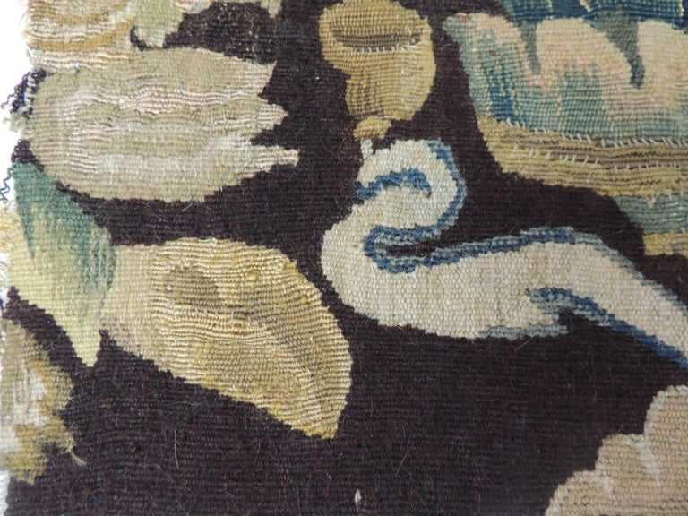 19th century fragment of green and brown verdure tapestry. This fragment depicts a floral bouquet in shades of brown, hunter green gold, blue and natural. The Aubusson tapestry manufacture of the 17th and 18th centuries managed to compete with the