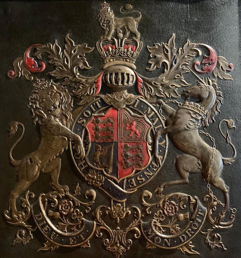 This elegant antique embossed leather shield panel was created in England circa 1870; square in shape and set in the original oak frame embellished with gilt molding, the crest depicts the Royal coat of arms of the United Kingdom with a lion and