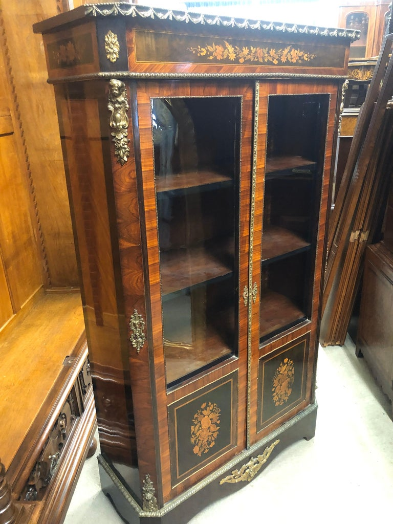 Beautiful French display cabinet Inlaid in a fine and elegant way with floral motifs and accompanied by bronze applications, display cabinet with three adjustable shelves. In wood of kingwood and rosewood, the inlays are in fruit woods. Very small