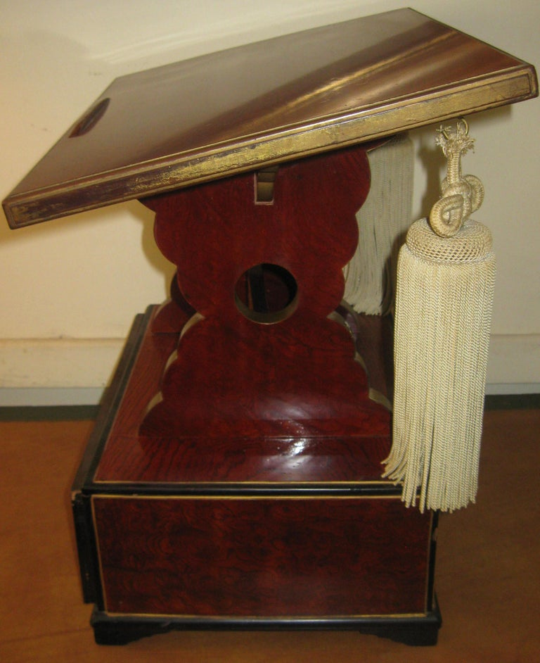 Unusual carved wooden book pedestal from a fraternal order lodge. Features include faux bois painted finish with gold and ebony highlights, slant top, bracket feet, scalloped supports and fancy silk tassels. One drawer with original brass pull.