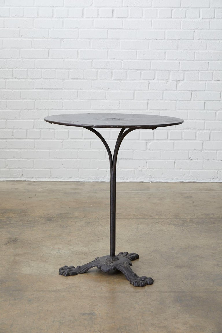 Distinctive French 19th century iron pub, bistro, garden, or café table. Made in the Art Nouveau period featuring a thick round iron top signed Laine. Supported by a column made of three thick iron rods. The base has a French depose patent mark and