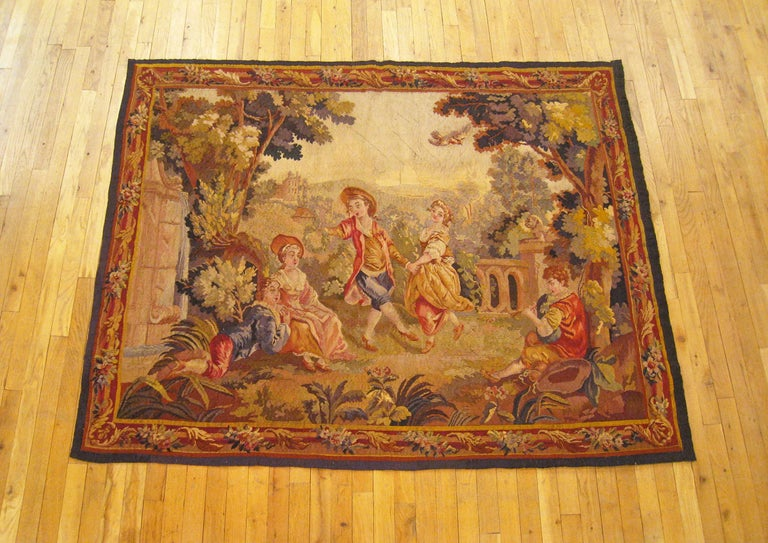 A French Aubusson tapestry from the 19th century, depicting several young courtiers spending a leisurely afternoon gaily dancing and carousing within the splendidly maintained verdant palatial grounds. Within a winding border of flower and acanthus