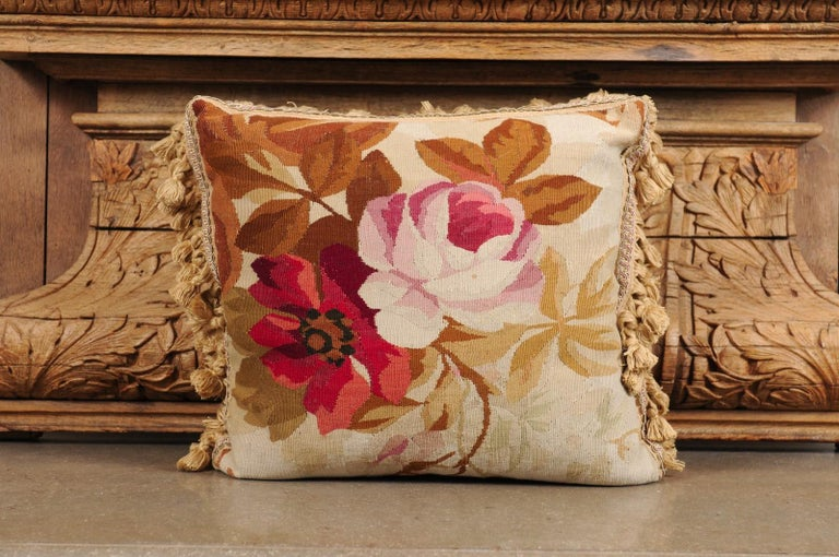 A French 19th century Aubusson tapestry pillow, with floral décor and tassels. Created during the 19th century in the Aubusson tapestry manufacture located in central France, this pillow features a pink rose and a red flower, perfectly accented by