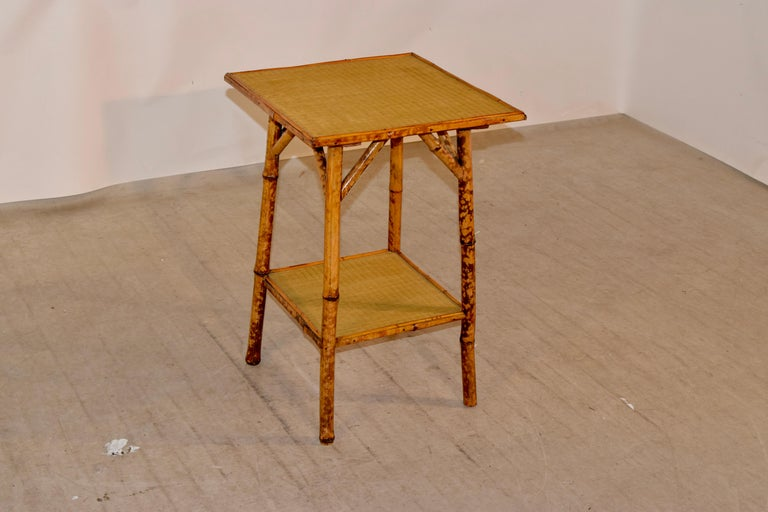 19th century tortoise bamboo table from France with a rush covered top and lower shelf.