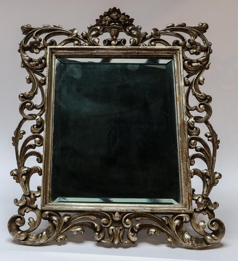 Ornately carved 19th century Baroque style vanity or wall mirror of silver giltwood and beveled glass. Can also be hung on the wall with the attached wire.