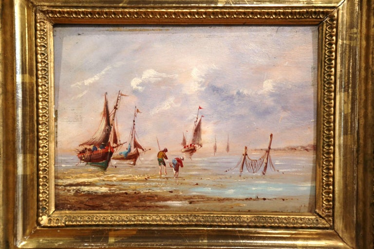 Set in the original carved gilt frame, this small oil painting on board was created in France, circa 1860; it features a typical fishing scene on the Brittany coast, with two people picking shellfish and sailboats in the background. The painting is