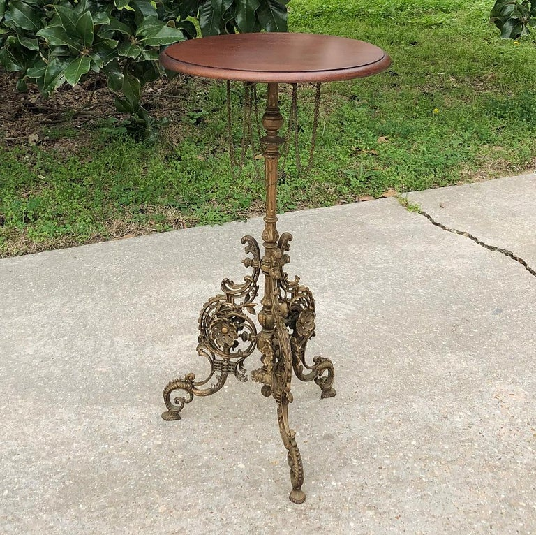 19th century French Belle Époque cafe table with painted cast iron base is a remarkably detailed work of art! Under the unassuming round walnut top is where the magic begins, with decorative chairs looped in a circle around the central shaft, which
