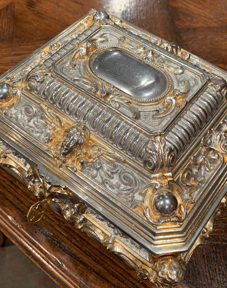 Place this elegant antique silver box in your master bath to keep your jewelry safe and organized. Crafted in France, circa 1880, the two-tone ornate rectangular casket sits on four scroll feet and has four bow sides over a raised top; the box