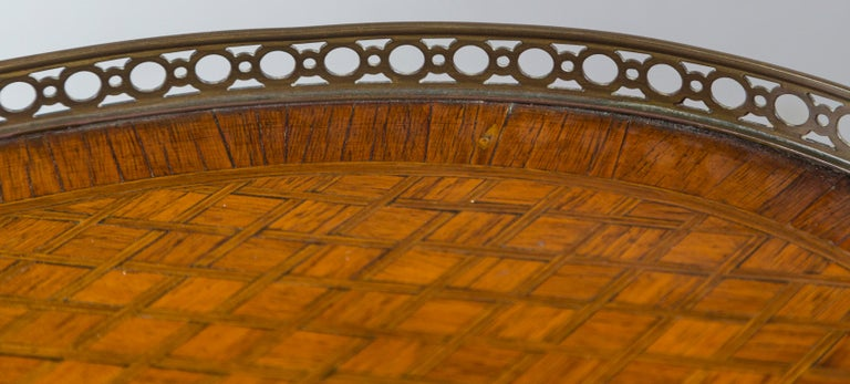 The top and the lower shelf inlayed in a geometric pattern with crossing lines of possible sycamore in the light mahogany. The apron and drawer front of the same inlays. A three quarter bronze gallery at the top with a bronze band on the lower