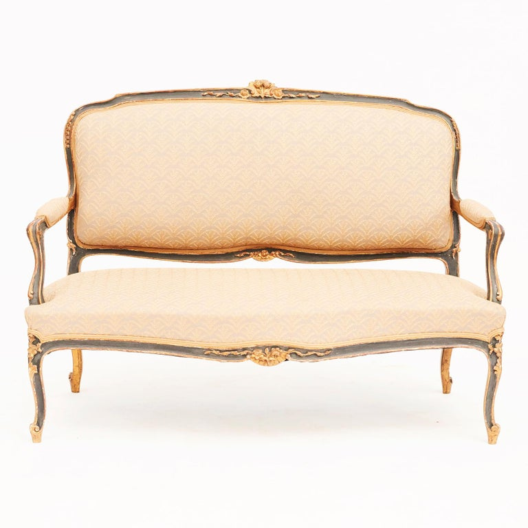 French Canapé sofa in Rococo / Louis XV style. Black and gold painted oak. Upholstered with gray linen fabrics with golden embroidery.