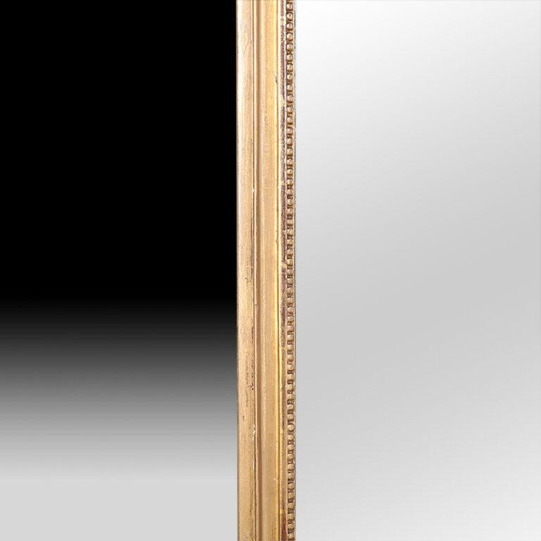 A 19th century French gilt-framed wall mirror with urn detail.
