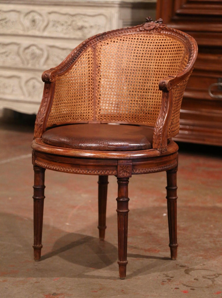 Decorate a study or office with this elegant antique fruitwood desk armchair. Crafted in Provence, France, circa 1870, the desk chair stands on four tapered and fluted legs decorated with floral rosettes at the shoulders, over a carved apron with