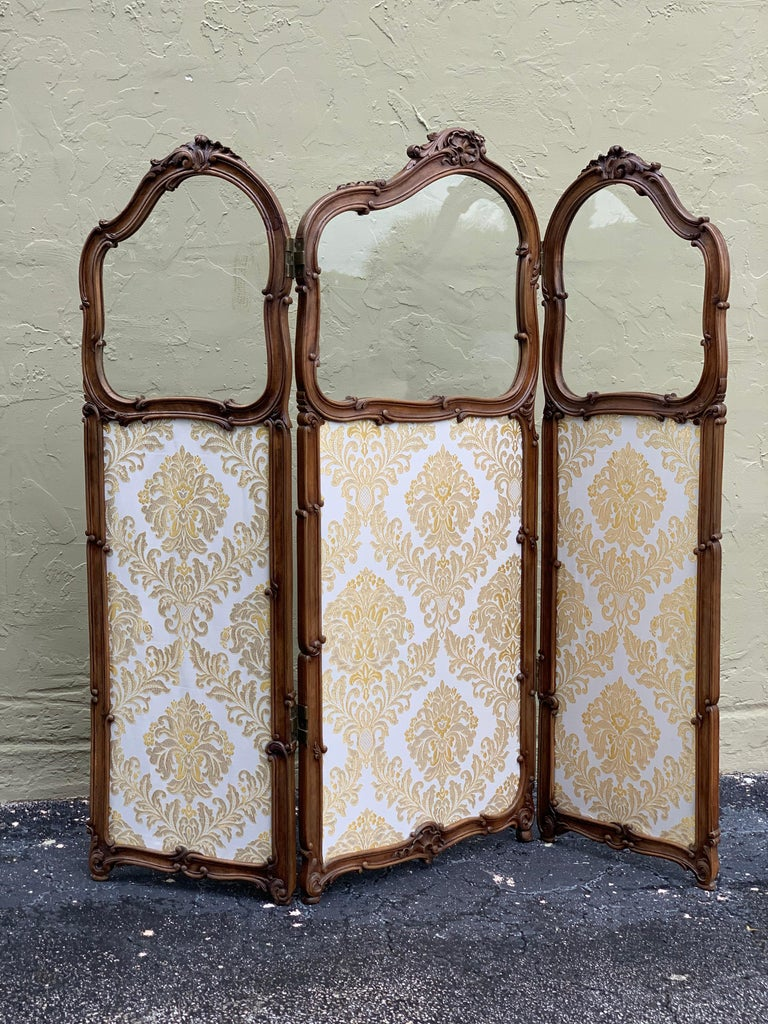 This lovely and delicately designed French carved walnut and gilt three-fold screen is circa 1890 and features the original bevelled glass panels on the top. Recently upholstered.