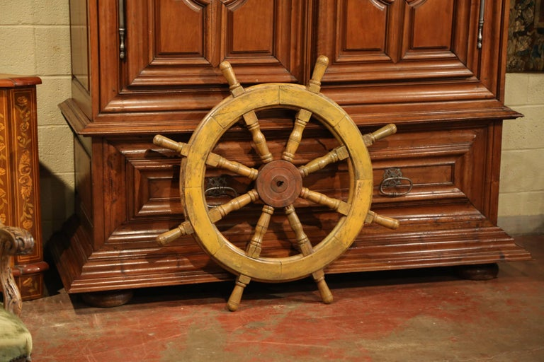 This large antique wooden ship wheel was carved in France, circa 1880. The traditional, fruitwood nautical object has its original metal brace around eight turned spindles with handles. The traditional marine accessory is in excellent condition with
