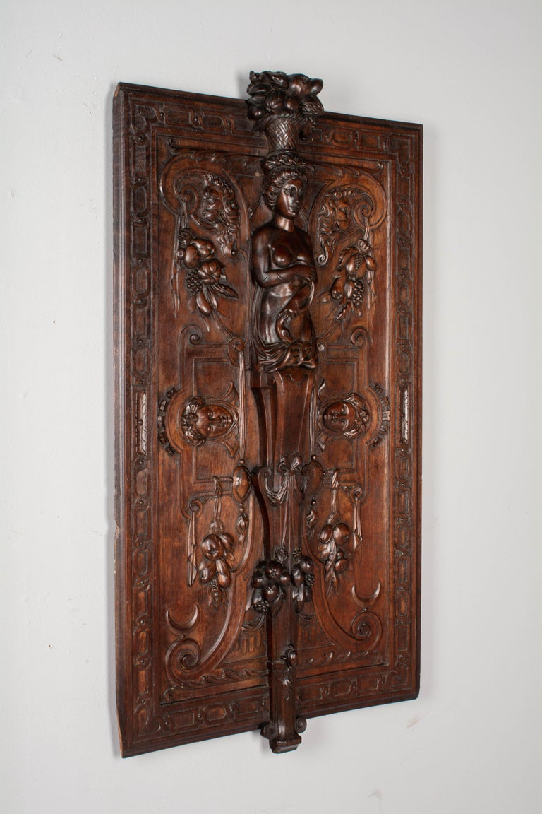 A 19th century French Renaissance Revival decorative wall panel made of solid hand carved walnut. Beautiful three dimensional details including a large central caryatid figure with fruit basket flanked by lions and hanging fruit swags. Fine quality