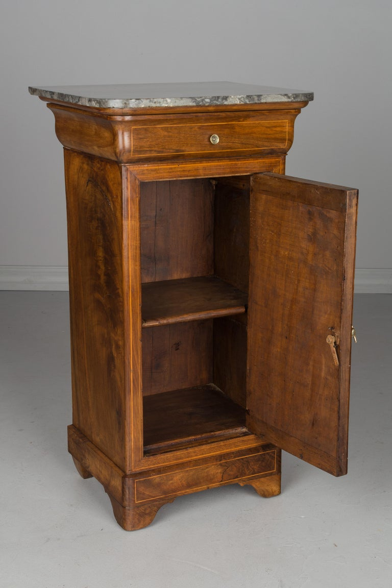 An early 19th century French Charles X side table or nightstand, made of walnut with fine inlay trim. Beautiful quality to the wood, the sides each with similar large knots. Waxed finish. Single dovetailed drawer with brass knob. Cabinet door with