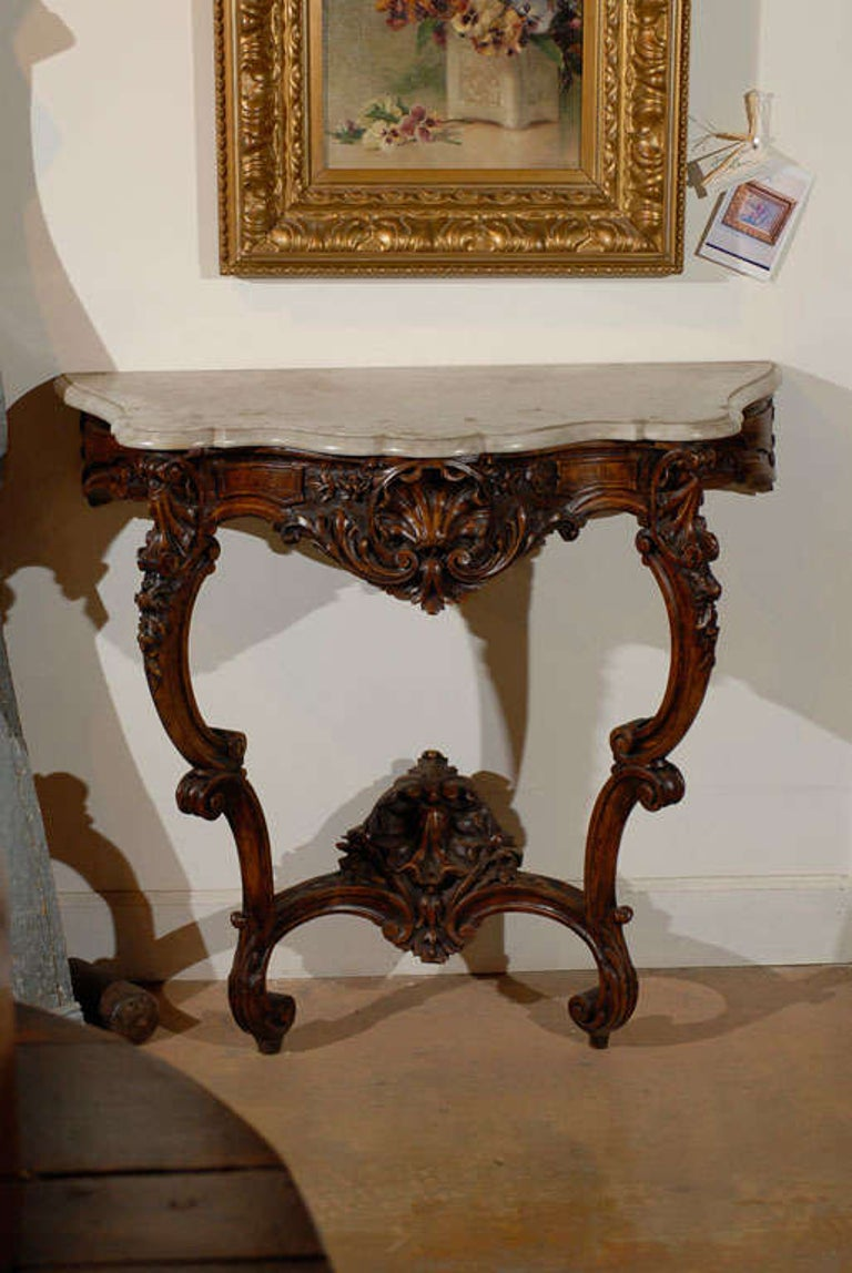 A French Rococo style carved wooden console table from the 19th century, with marble top, cabriole legs and cross stretcher. Born in France during the politically dynamic 19th century, this console table showcases the stylistic characteristics of