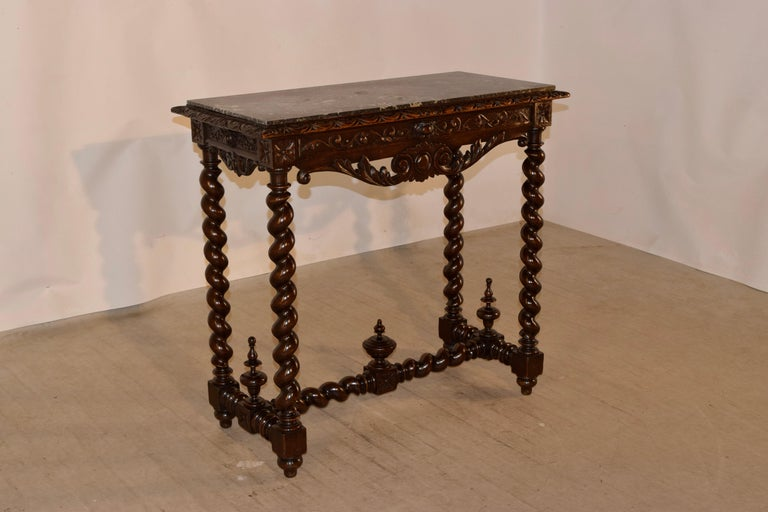 19th century French marble topped console table made from walnut. The top is black marble, which is removable and rests upon a solid walnut base. The table base is wonderfully hand carved decorated on the beveled edge around the top and the apron as
