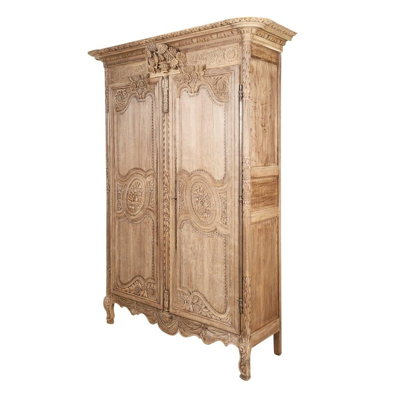 French Country Louis XV style bleached armoire de mariage, circa early 1800s, handcrafted of French oak near Saint-Lô, a commune in the Normandy region. This beautiful 19th century wedding or marriage armoire features symbolic carvings typical of