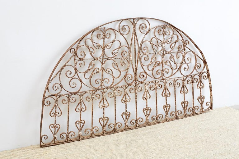 Decorative 19th century French wrought iron transom grille made in the Art Nouveau taste. Features a demilune form with scrolled circles and grates. Very solid and heavy with a beautiful distressed patinated metal finish and old paint remnants.