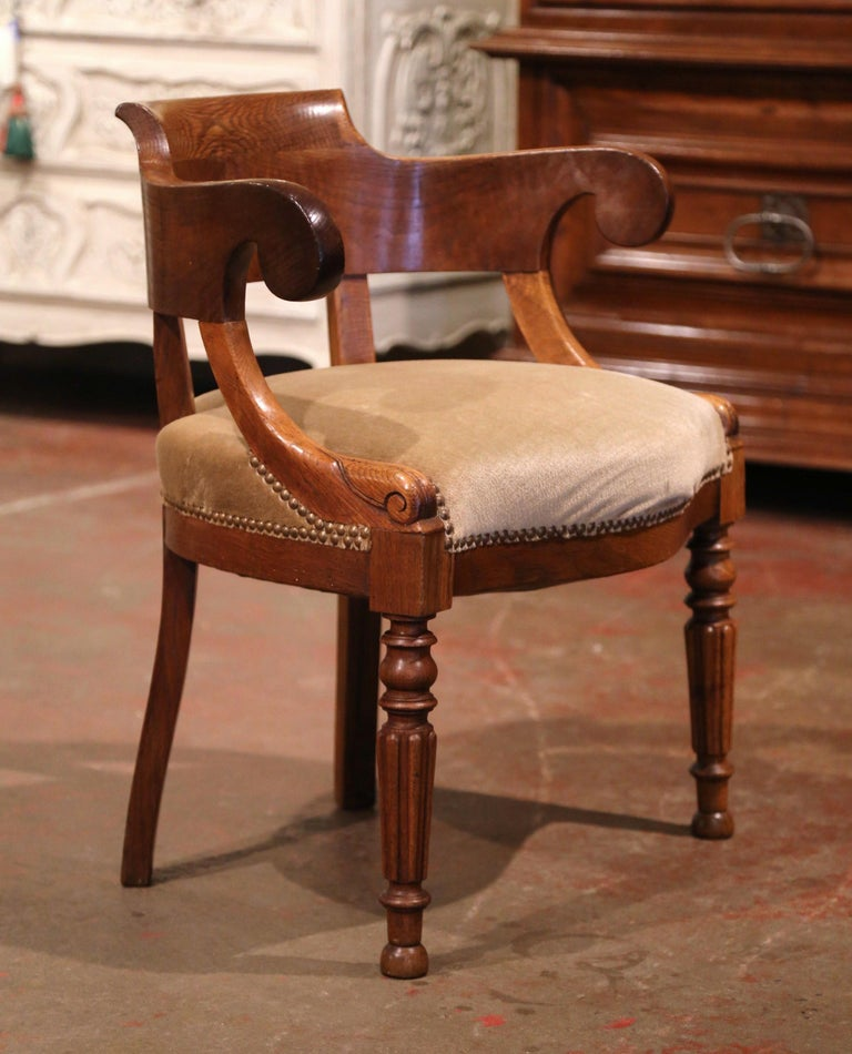 The sophisticated antique armchair would make an elegant yet subtle statement behind a man or woman's desk. Crafted in France circa 1880 and made of chestnut and oakwood, the carved armchair sits on front turned and tapered legs; the chair features