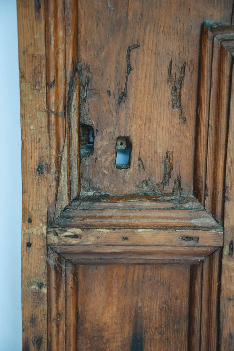 This is a French door form the 19th century. Strong and sturdy the door features hand forged iron hinges and the remnants of a lock. A wonderful piece to use in your home as a cabinet door or simply lean against a wall as a piece of art.
