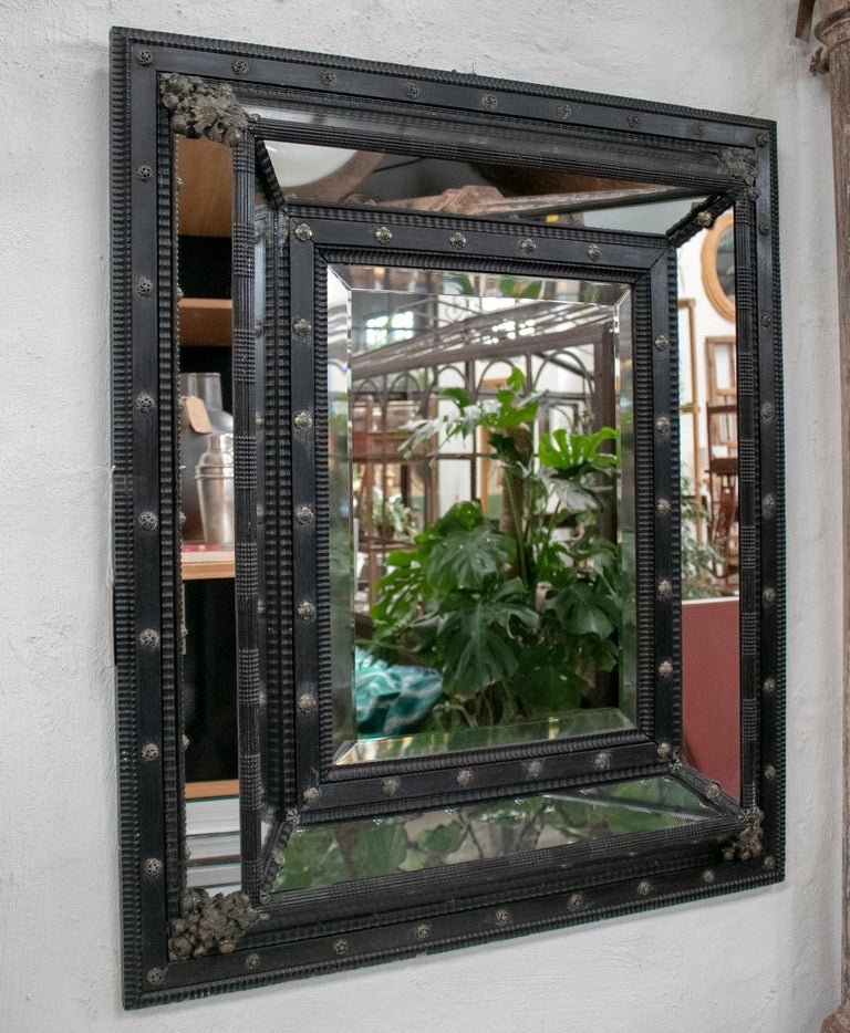 19th century square French ebonized mirror with bronze decorations.