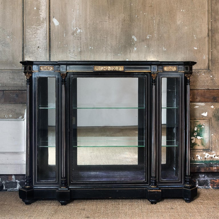 A mid-19th century French ebonized and inlayed display cabinet, of breakfront form, the (later) mirrored top above frieze with cast bronze Grecian bas-relief panels, the body with mirrored back and all-round glazing intersected by Corinthian
