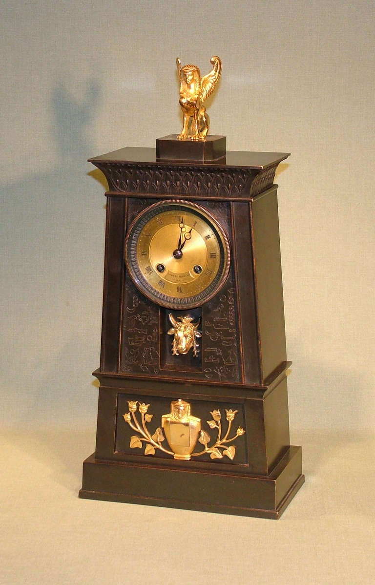 """A French Empire bronze and ormolu clock in the Egyptian style with 8 day silk-suspension striking movement by Hemon a Paris, also marked """"Ledure Bronzier"""", enclosed in bronze obelisk tower decorated with hieroglyphics and mounted with recessed"""