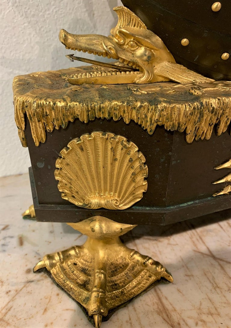 Extraordinary 19th century French Empire gilt and patinated bronze allegorical mantel clock. Chronos (Father Time) is portrayed in a boat holding an hourglass and scythe. The boat is being steered by Amour. The base fashioned as an oceanic surface,