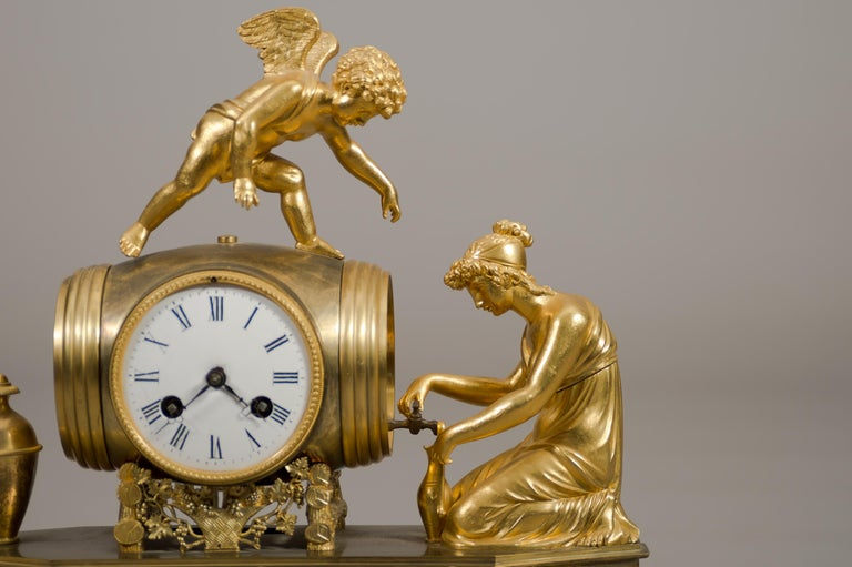 A fine Early 19th century French Empire ormolu bronze mantel clock.   Depicting a winged cherub standing atop a barrel while a kneeling lady pouring wine into a vase. Having a white enamel dial with Roman numerals, and a movement with a silk wire