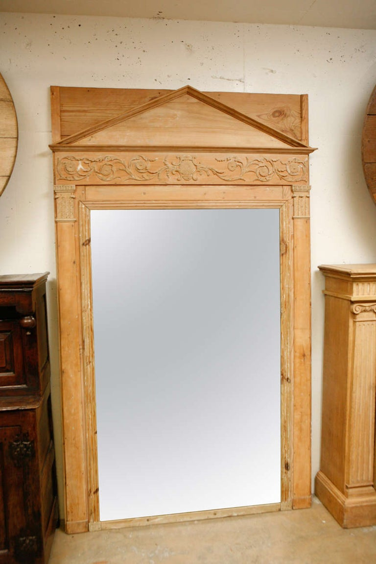 19th century French Empire pine mirror with neoclassical pediment top. Exquisitely carved, all original pine frame Empire mirror with a foliate scroll motif frieze, flanked with lower Corinthian capitol pilasters surrounding an inner border of stars.